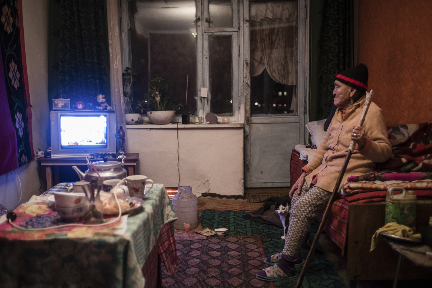 Pensioner Saken Kapysova watches TV in an apartment in multistory building built during the Soviet era for Makmalzolo plant employees