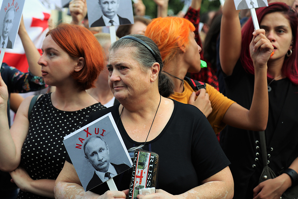 "Protesters held posters with photos of Georgia's main antagonist in the war, Russian President Vladimir Putin, along with a caption that translates, roughly, ""go f--- yourself."" (Photos by Giorgi Lomsadze)"