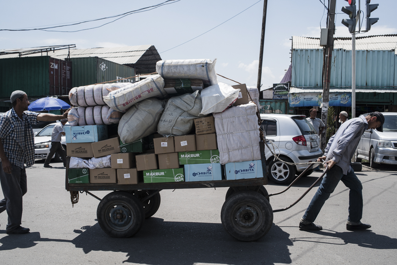 Dayworkers carry goods outside the Omart XXI Century market in Kara-Suu.