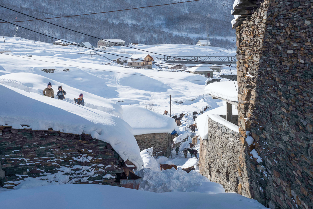 Children shovelling snow off their roofs in Ushguli