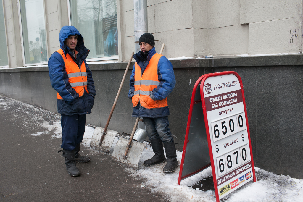 Migrants in Russia with exchange rate sign