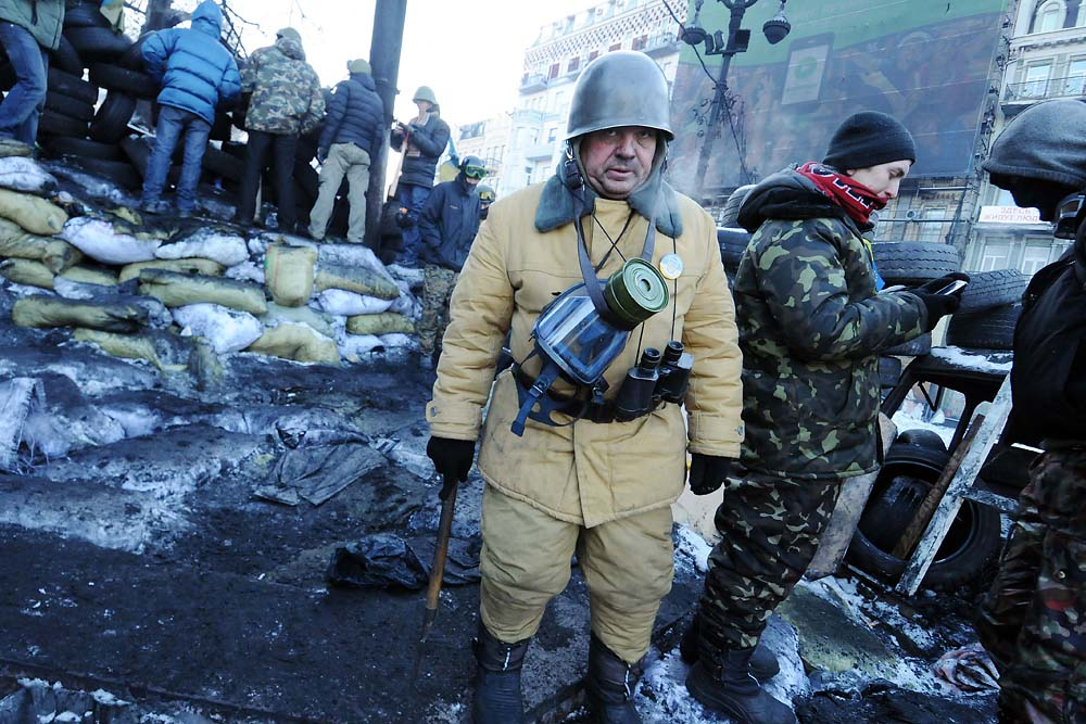 A government opposition supporter guards a barricade in Kiev at the height of the standoff in January. (Jonathan Alpeyrie)