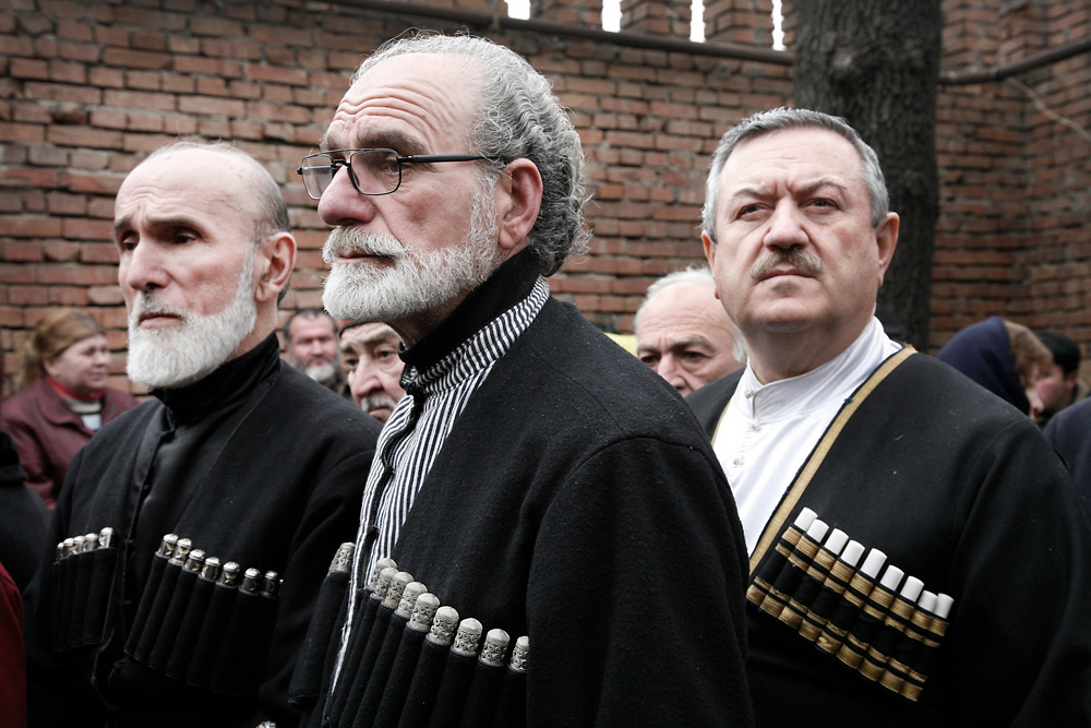 Tbilisi residents, wearing traditional chokhas, attend a funeral service for Georgia's late President Zviad Gamsakhurdia.