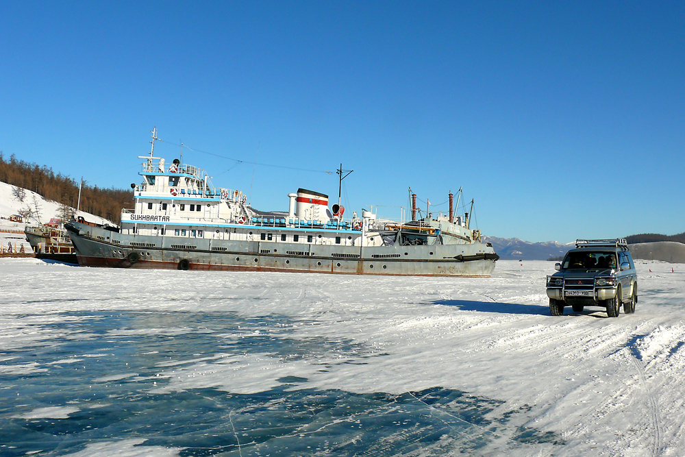 An SUV drives past the passenger ship Sukhbaatar stuck in the thick ice on Khovsgol Lake in Mongolia's northernmost province.
