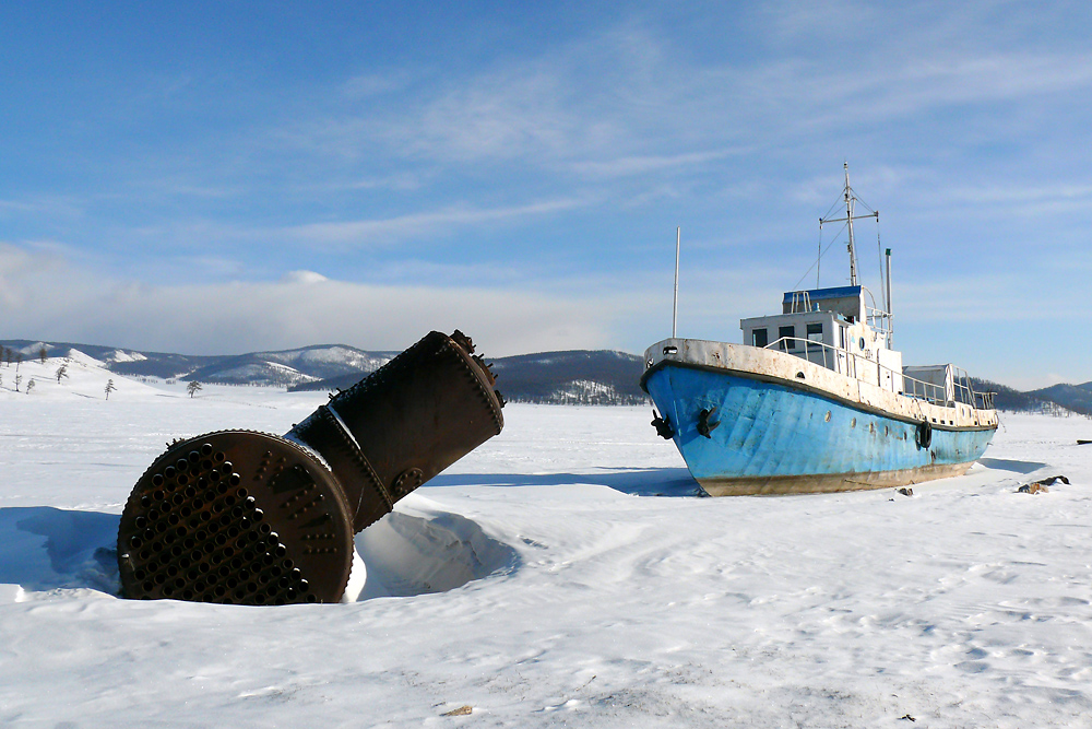 An old oil tanker engine lies abandoned in ice next to a private tourist boat, which remains frozen for half the year.