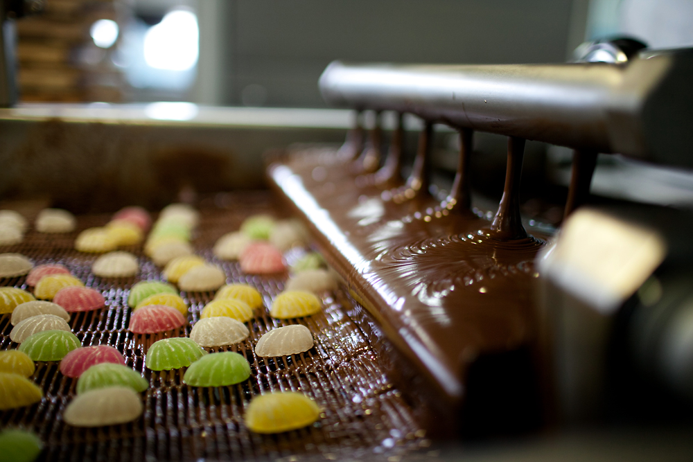 Chocolate is poured over lurid-colored jelly candies.