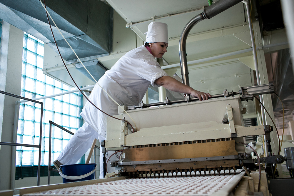 A worker monitors as a machine squirts chocolate into molds.