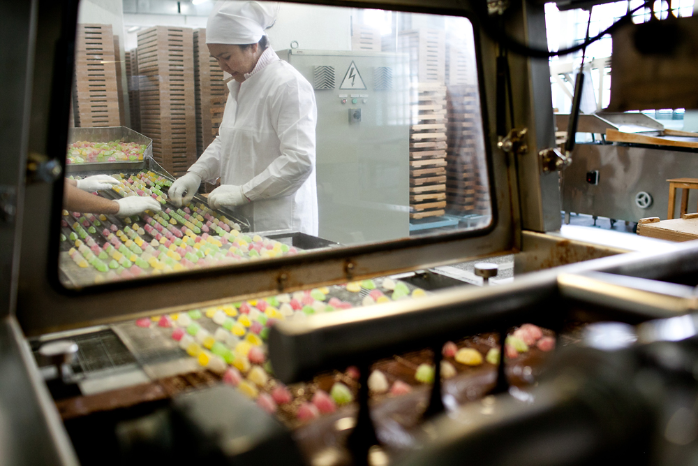 Workers sort candies before they are covered in chocolate.