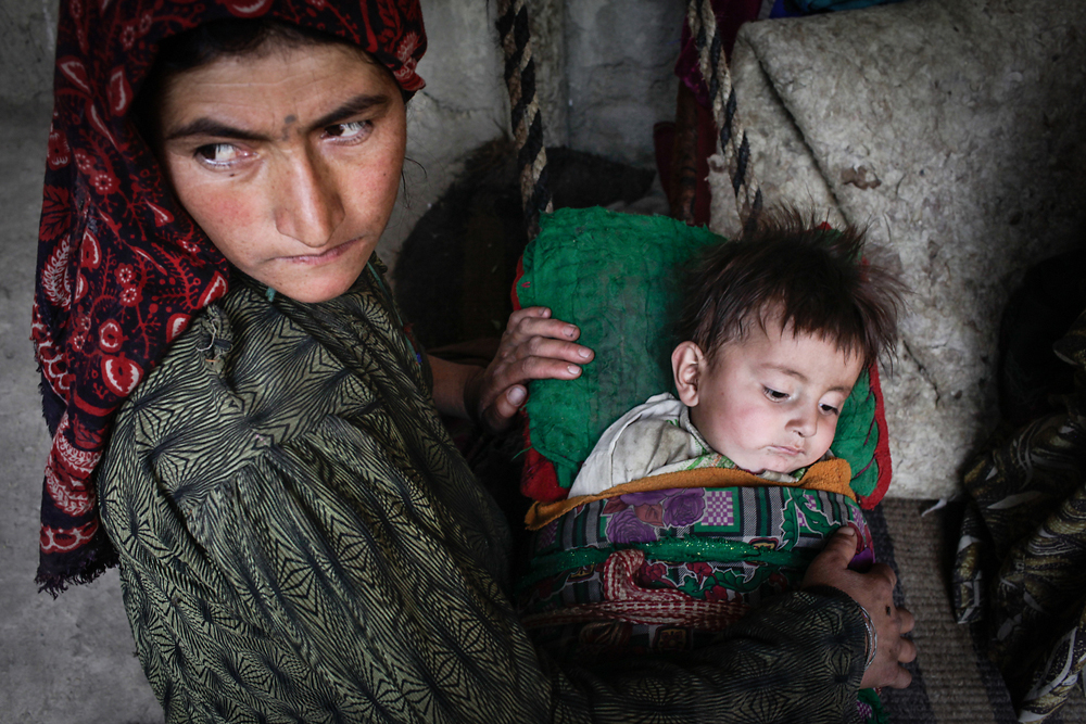 An Afghan mother sits outside her home in the remote Afghan village of Khandud, which sits on the bank of the Panj River.