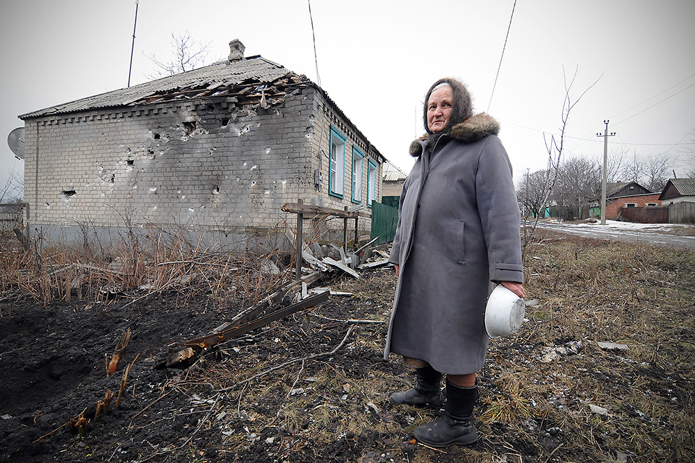 A woman stands in front of a war-damaged house in Debal'tseve, Ukraine. (Photo: Jonathan Alpeyrie)