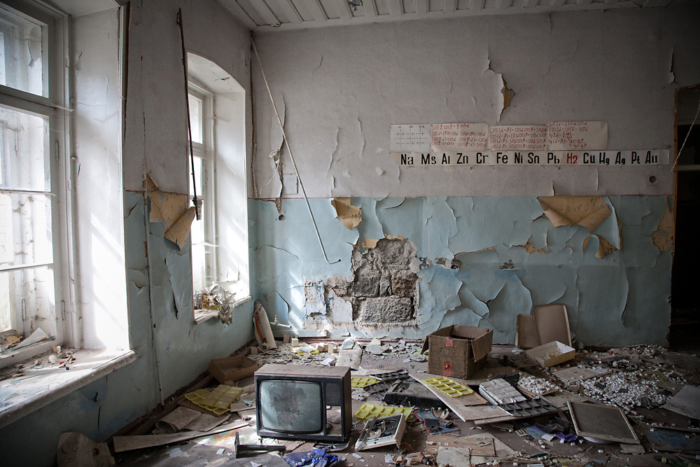 Paint peels from the walls and garbage litters the floor of the abandoned school on the former Russian army base.
