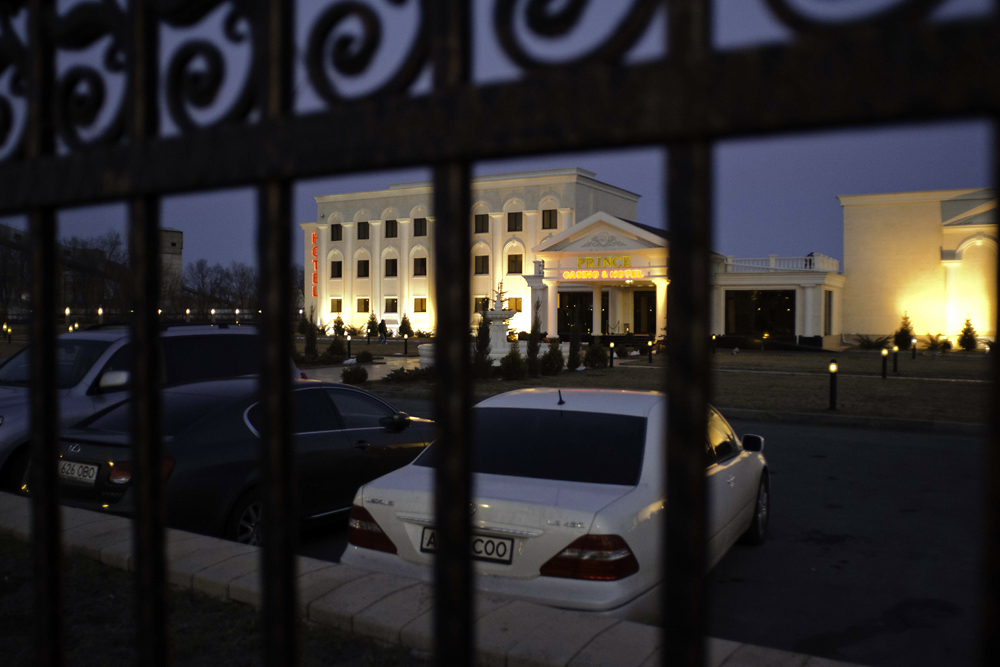 Luxury cars sit outside the gated Prince casino in Kapshagay.