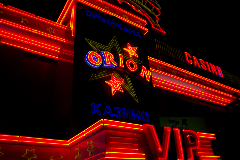 Outside the VIP entrance, colored neon lights flash and blink on the facade of the Orion casino.