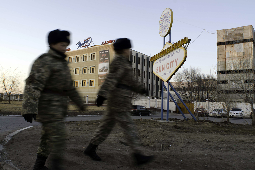 Female Kazakh soldiers walk past the Flamingo casino and an advertisement for the Sun City casino.