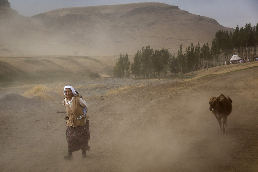One of the original refugees, a Kyrgyz grandmother, walks in a dust storm near Ulupamir.