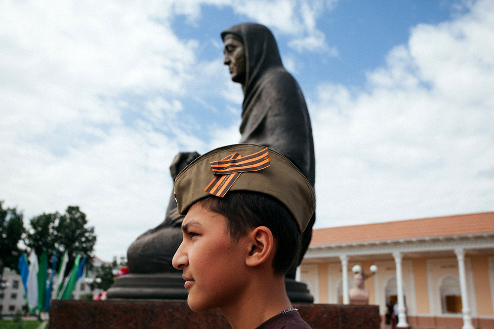 A boy wearing a military cap stands near Andijan's Grieving Mother WWII Memorial on Victory Day. (Photo: Timur Karpov)