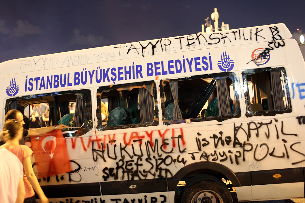 Graffiti covers a city bus destroyed by the anti-government protest.