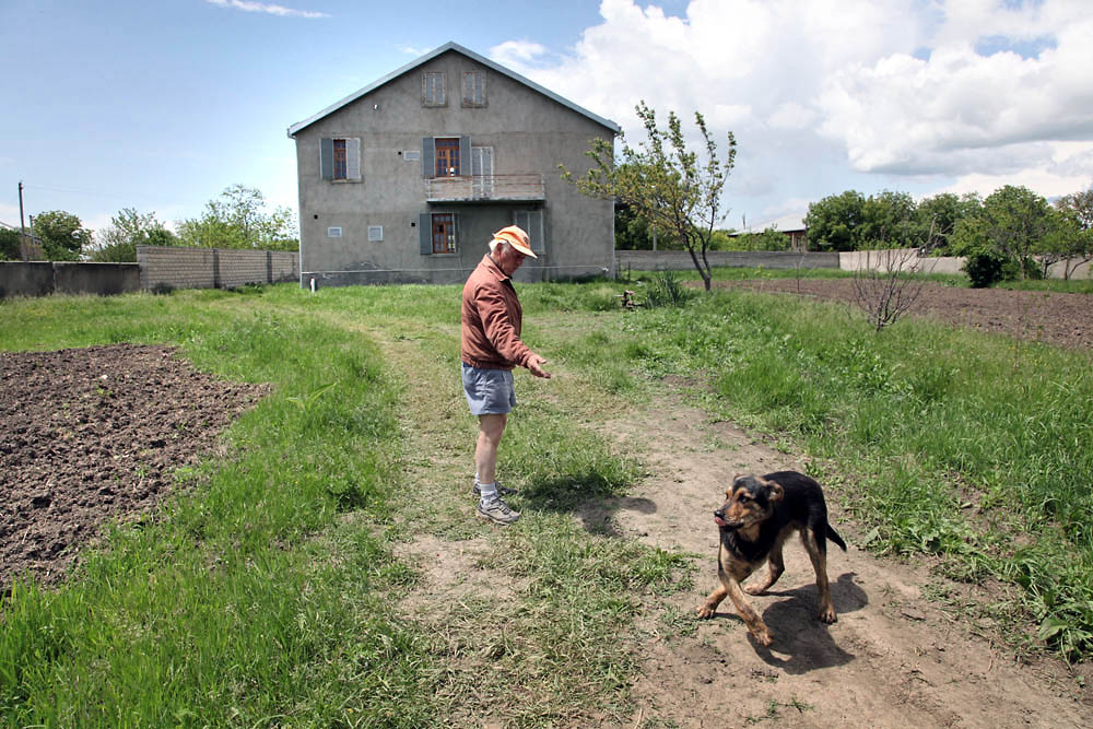 Kemp plays with his dog in front of the house he rented in the village of Sartichala.