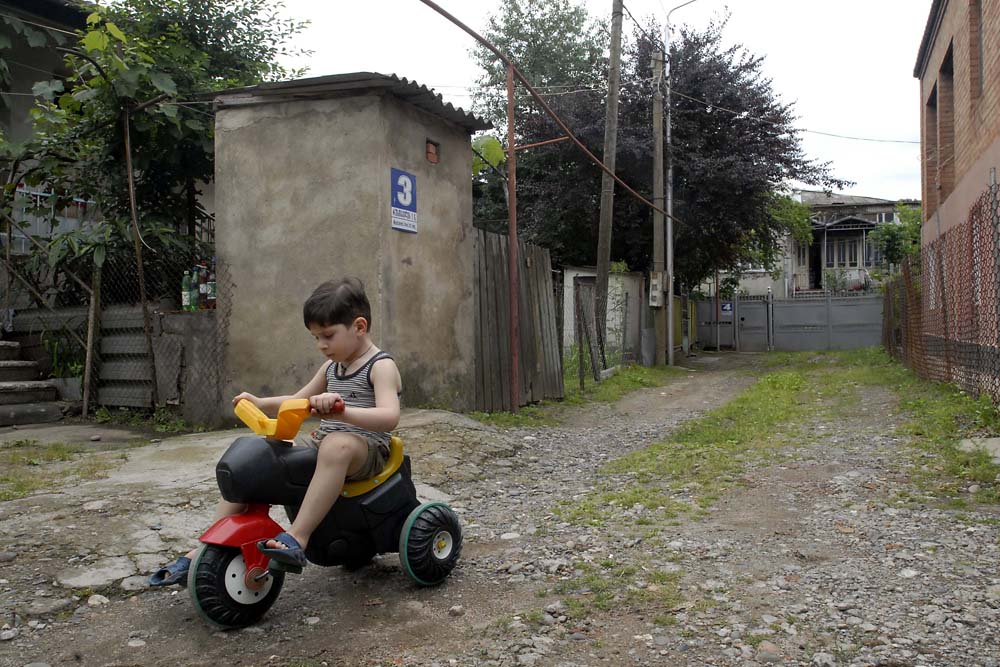 Giorgi, 4, plays in his yard on one of the quiet streets that branch off from Rustaveli Avenue, the main street.