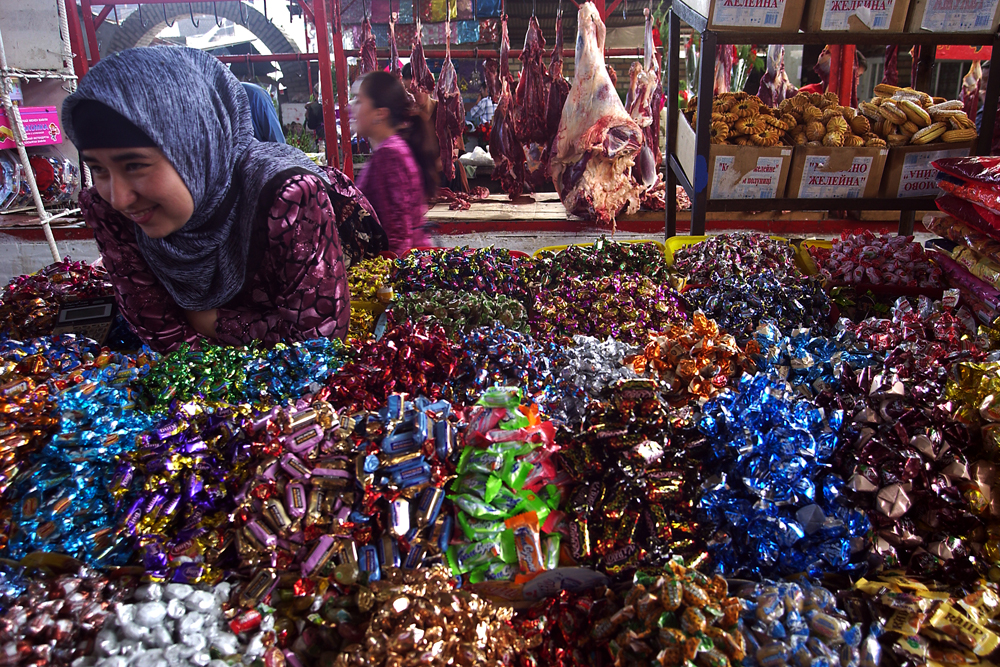 A woman awaits customers in need of varieties of chocolates and candies.