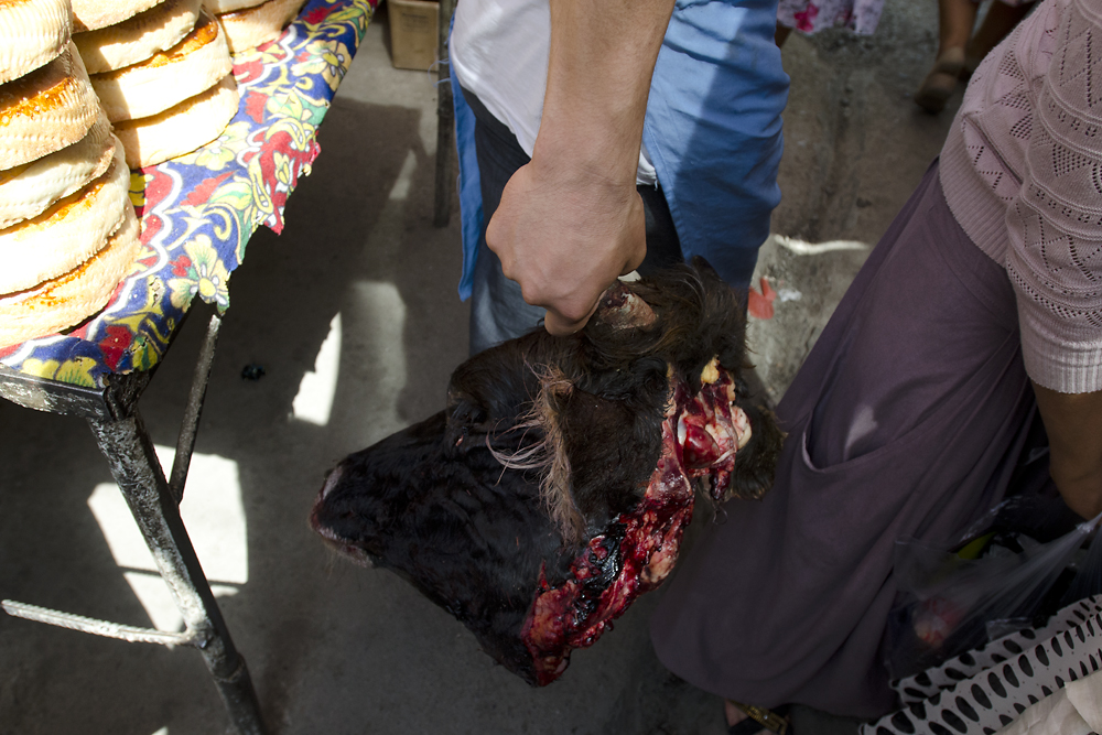 With a severed cow's head in hand, a butcher squeezes through a packed crowd of shoppers.