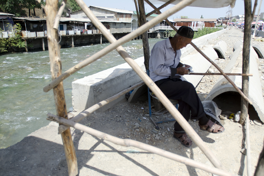 A man counts Kyrgyz som while sitting in the shade next to the Ak-Buura River, which cuts through the market.