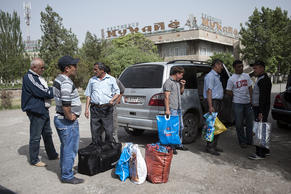 Migrant workers arrive in Khujand, Tajikistan, early in the morning for buses to take them to Russia for employment.
