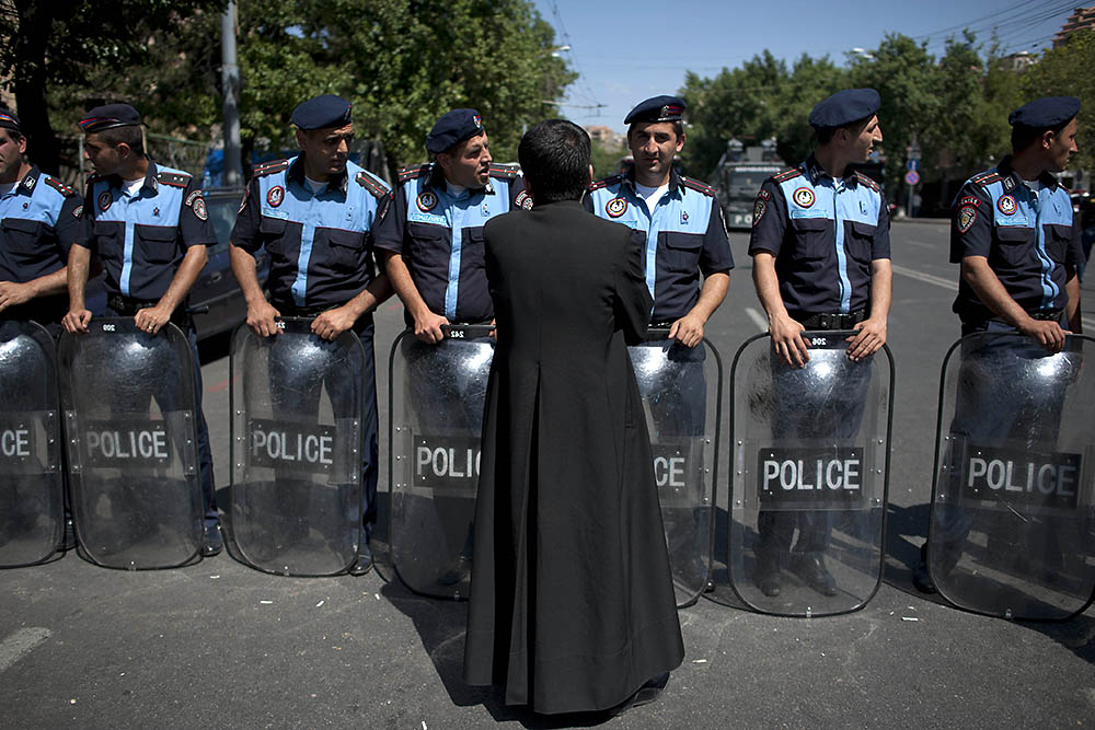 An Orthodox priest talks with police during protests against electricity price increases. (Photo: Nazik Armanakyan)