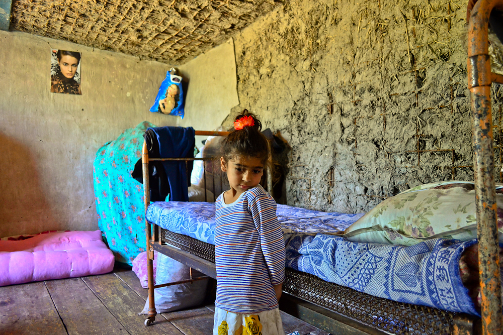 A girl continues to live with her siblings, mother and grandmother in  a flood-damaged, single-room hut in Urajaly.
