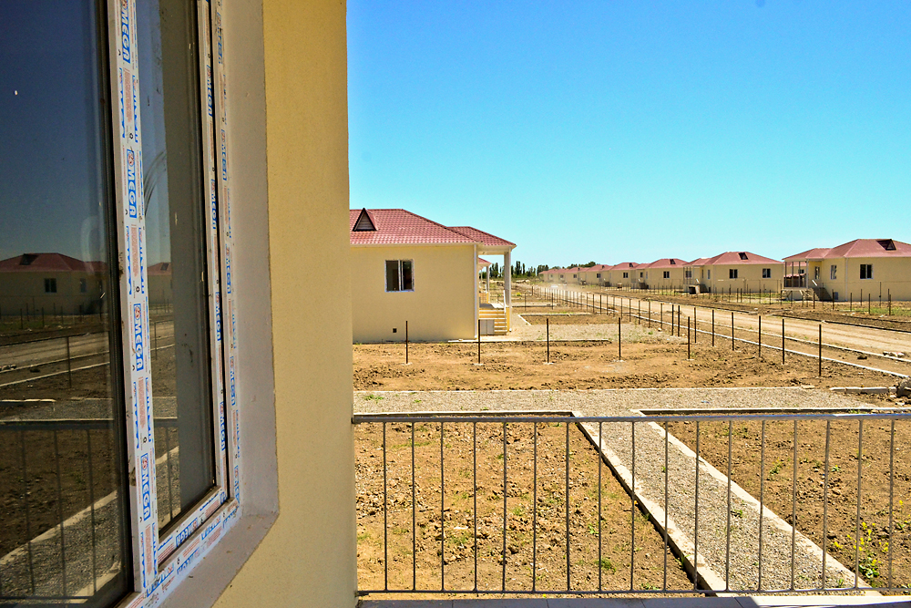 Thirty-eight new houses are nearing completion in Urajaly, but residents in the village say the new occupants remain a secret.