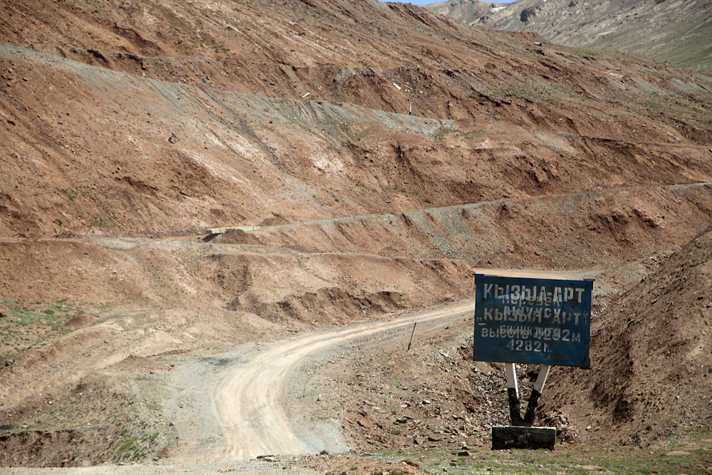 A sign marks the ascent on the Kyrgyz side to the 4,282-meter Kyzyl-Art Pass between Kyrgyzstan and Tajikistan.