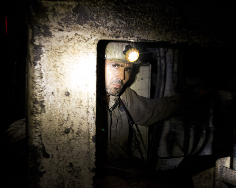 A worker rides along tracks in the depth of the mine.