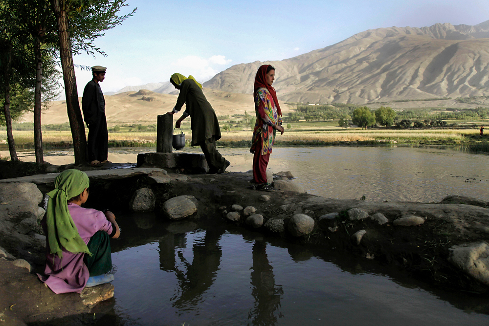 An Afghan woman gathers water at the village's central stream in Ishkashim, Afghanistan. (Diana Markosian)