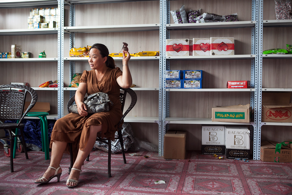 A Chinese woman sits in a shop on the Kazakhstani side that sells a little candy and Georgian wine.