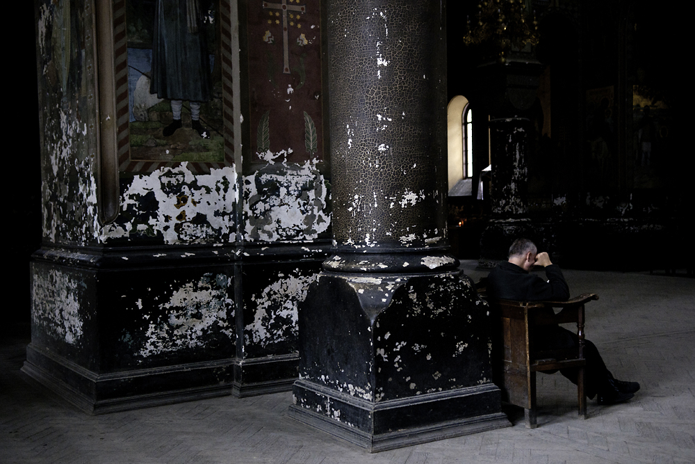 A man prays alone and in silence inside the main cathedral at Novy Afon.