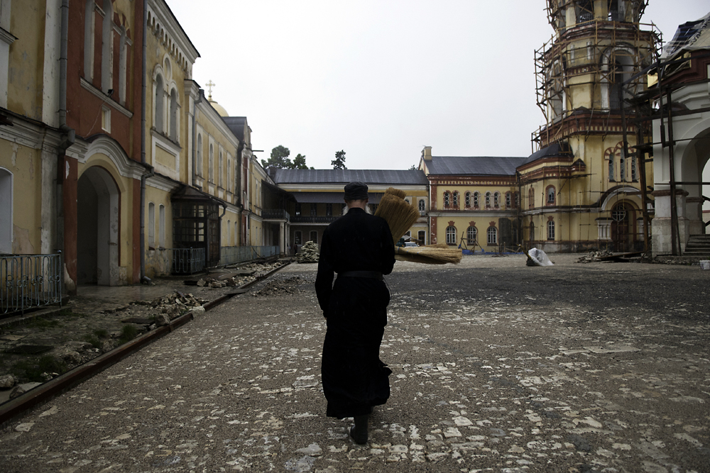 A monk carries brooms through the courtyard of Novy Afon, much of which is still under renovation with Russian money.