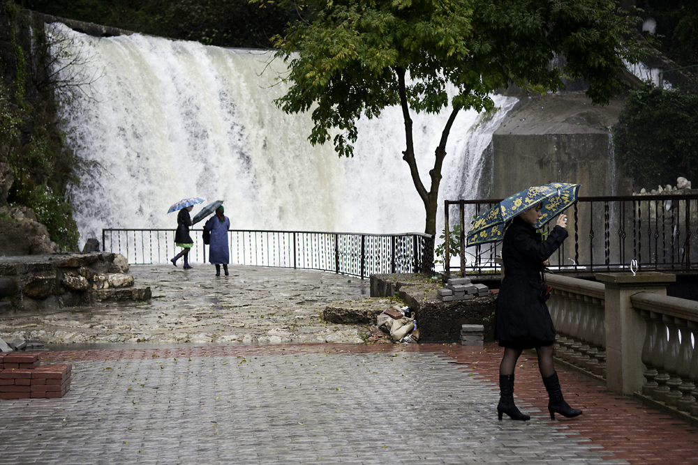 Russian tourists visit the waterfall next to the grotto and church of St. Simon the Zealot, located near Novy Afon.