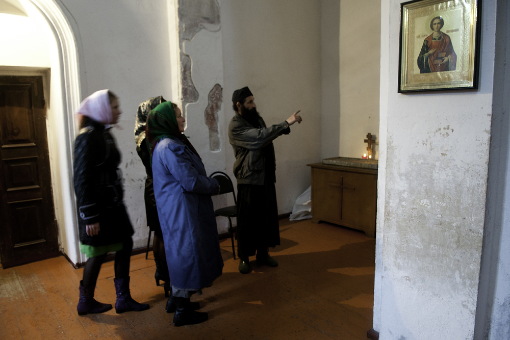A monk tells visitors about the various icons on display inside the Church of St. Simon the Zealot.
