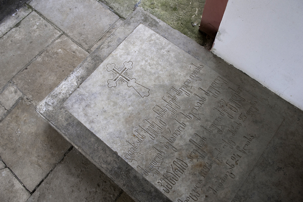 A grave at the Ilori church bears Georgian script on the solid rock covering.