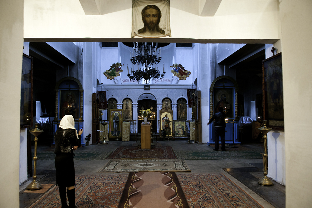 A woman prays inside the entrance to the cathedral in the Abkhaz capital, Sukhumi.