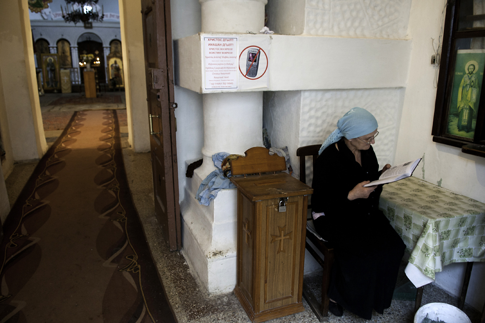 A woman reads a bible inside the Sukhumi cathedral, considered the center of the breakaway Abkhaz Orthodox Church.