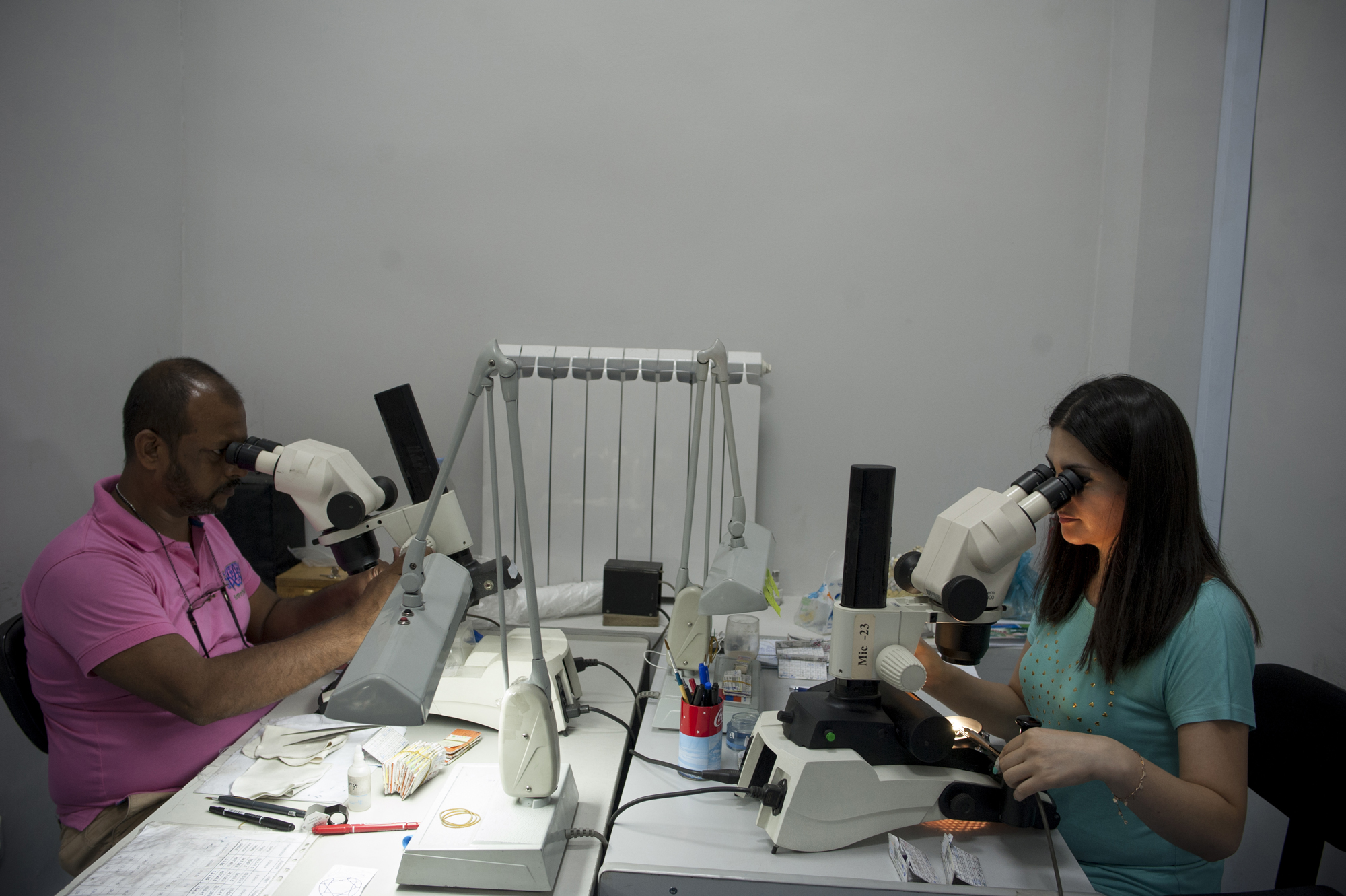 Using microscopes, Dimotech workers grade the refined diamonds for pricing and export.