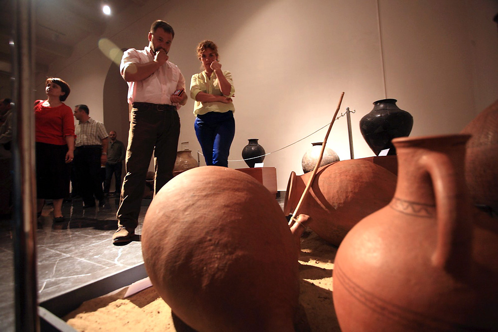 Visitors to the museum of wine in Tbilisi look at traditional kvevri clay vessels.