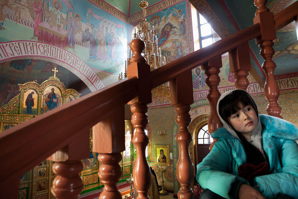 A young girl of mixed Russian-Mongolian heritage observes mass from the balcony wing of the church.