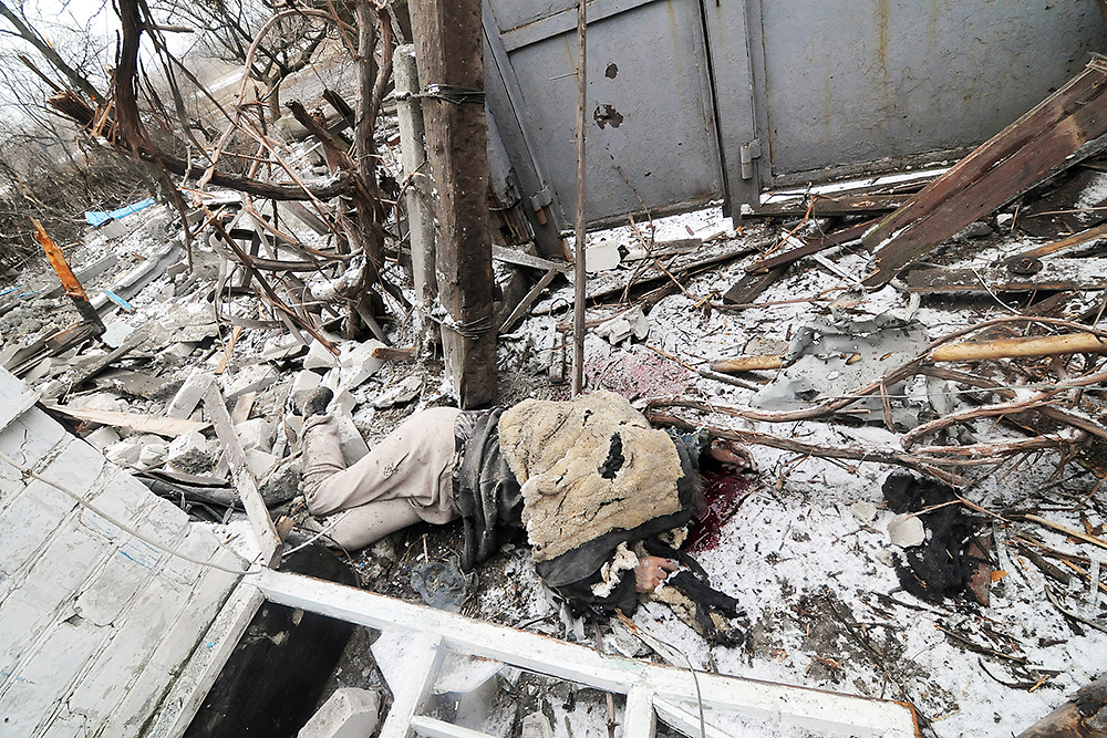 A killed resident of Debal'tseve, Ukraine, lays covered with a jacket in his bombed home. (Photo: Jonathan Alpeyrie)