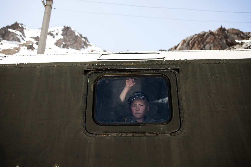 A young boy travels with parents inside a van, following sheep to summer pastures in Kyrgyzstan. (Konstantin Salomatin)