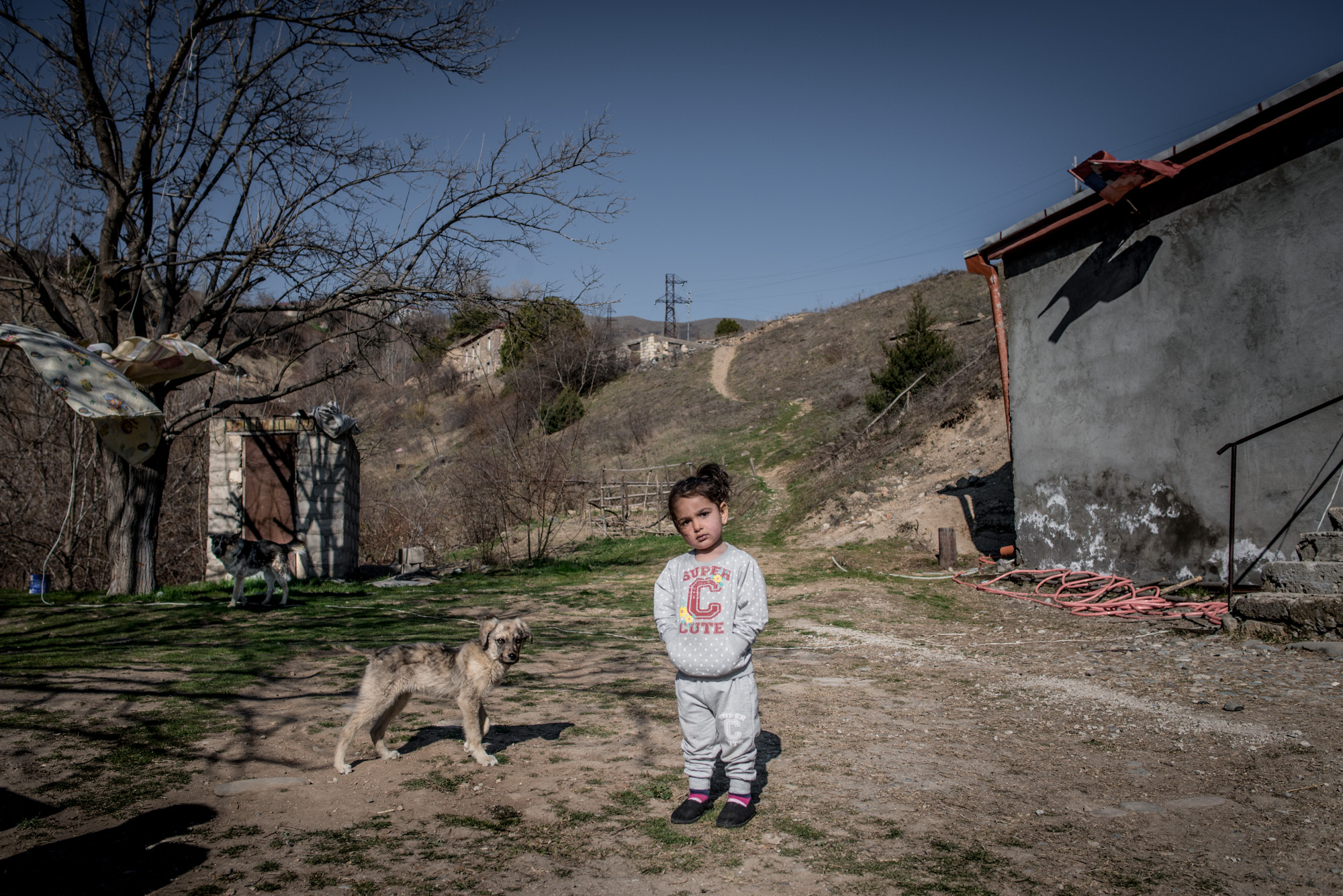Knarik, the daughter of Andranik Chaushyan and Kristine Khalatyan, stands outside the house that the family received in Lachin.