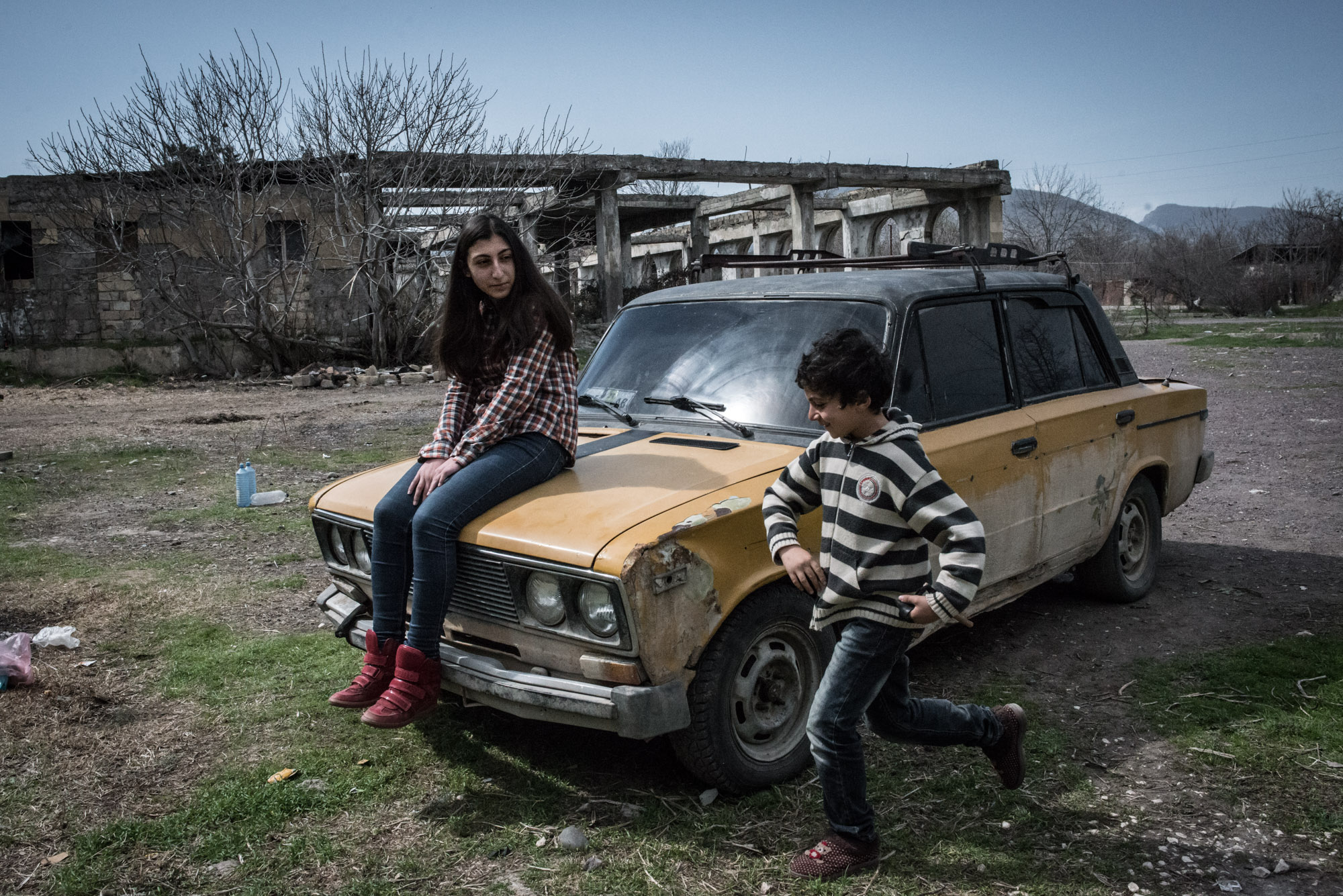 Anna Maria, 16, and George, 9, play in the backyard of their apartment block in Lachin.