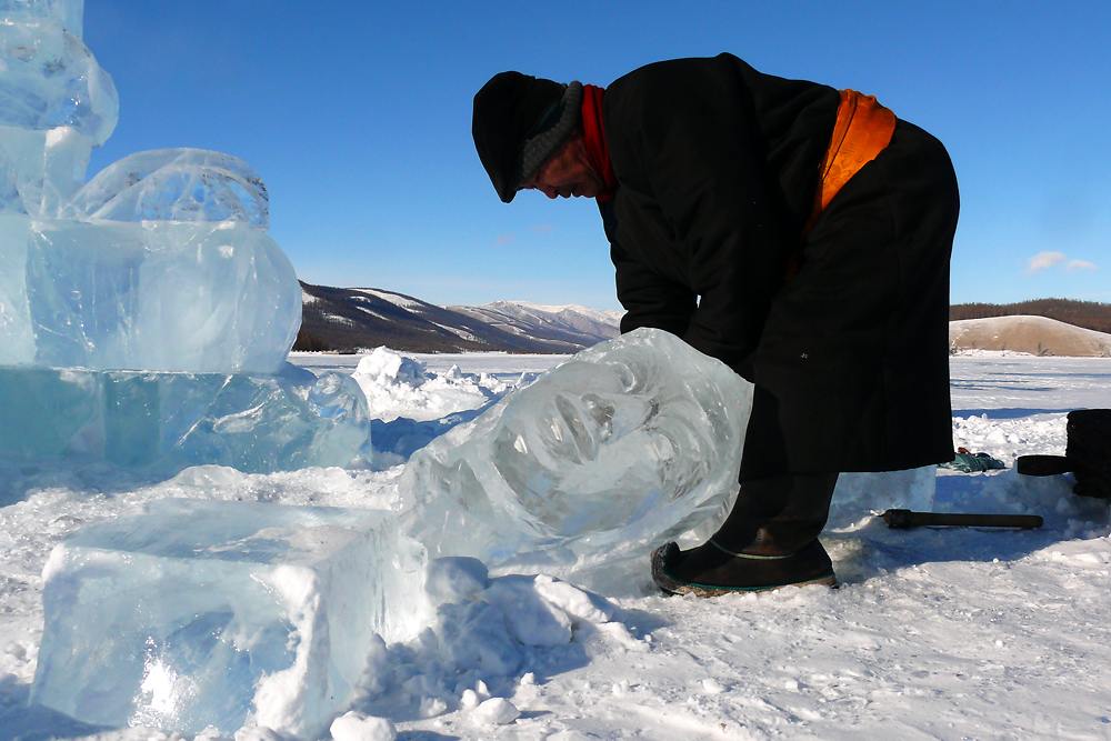 "Woodcarver turned festival ice sculptor, Batbayar finishes the head of his sculpture called ""Dalai Eej"" (Ocean Mother)."