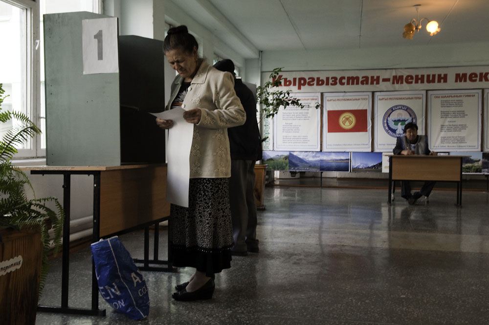 A women looks at the long ballot featuring 29 parties at a polling station in the Yuri Gagarin primary school.